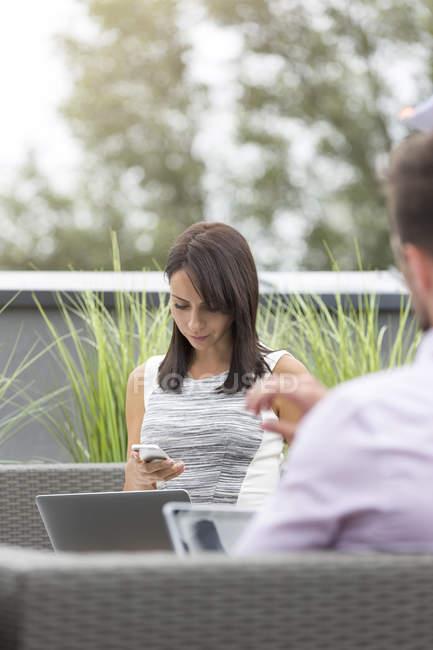 Два деловых людей, сидя на террасе на крыше, используя ноутбук и смарт-телефон — стоковое фото