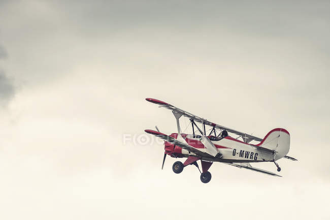 Biplano vintage no ar, céu nublado no fundo — Fotografia de Stock