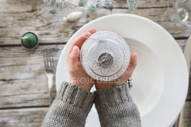 Cropped view of child hands holding Christmas bauble — Stock Photo
