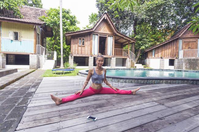 Индонезия, Бали, женщина, практикующая йогу у бассейна — стоковое фото