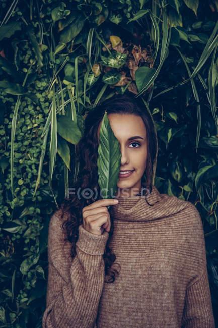 Улыбающаяся молодая женщина покрывает один глаз листком — стоковое фото