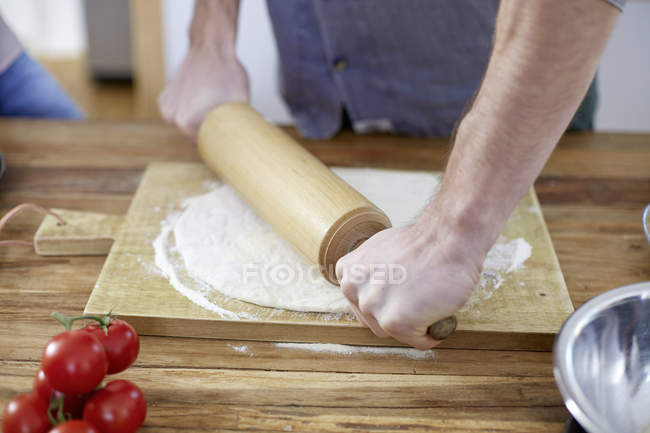 Man preparing dough with rolling pin — Stock Photo