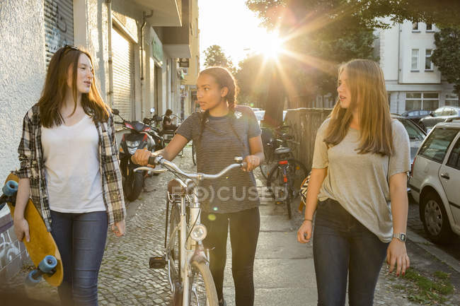 Three teenage girls on pavement with bicycle and skateboard — Stock Photo