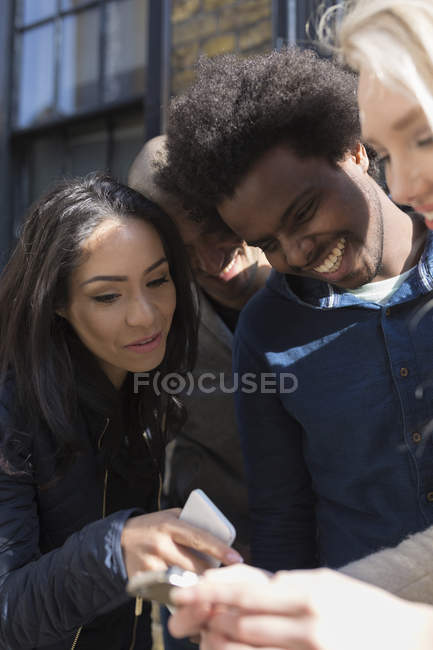 Happy friends sharing cell phone on street — Stock Photo