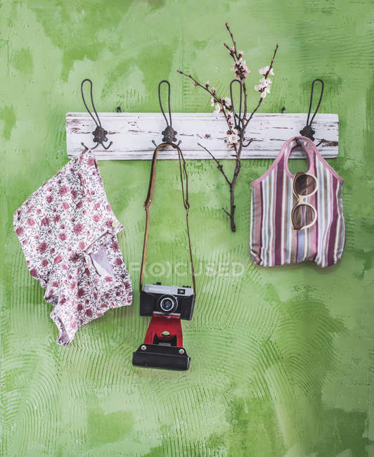 Spring items and old camera on wall coat rack — Stock Photo