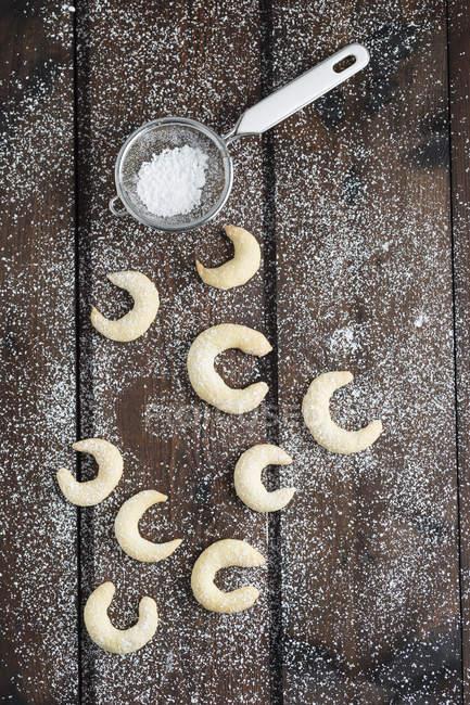 Galletas de almendra con glaseado de azúcar en la madera, colador - foto de stock