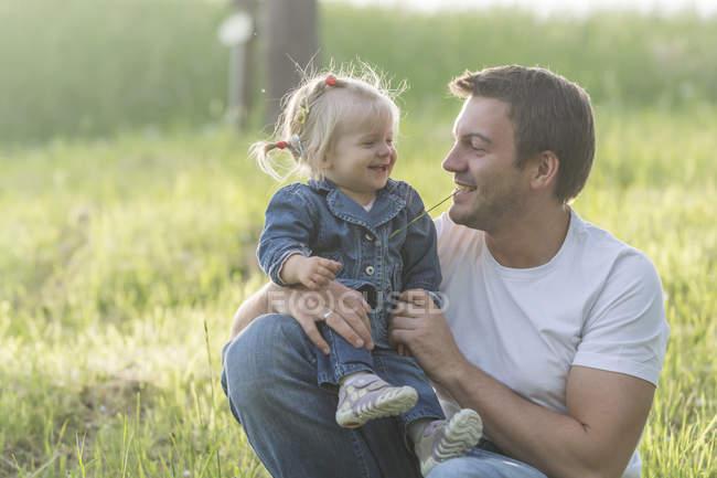 Père et sa petite fille s'amusent dans une prairie — Photo de stock