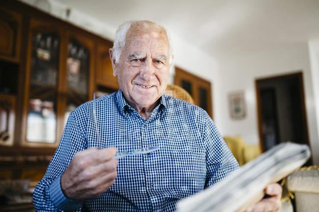 Senior man sitting with newspaper — Stock Photo