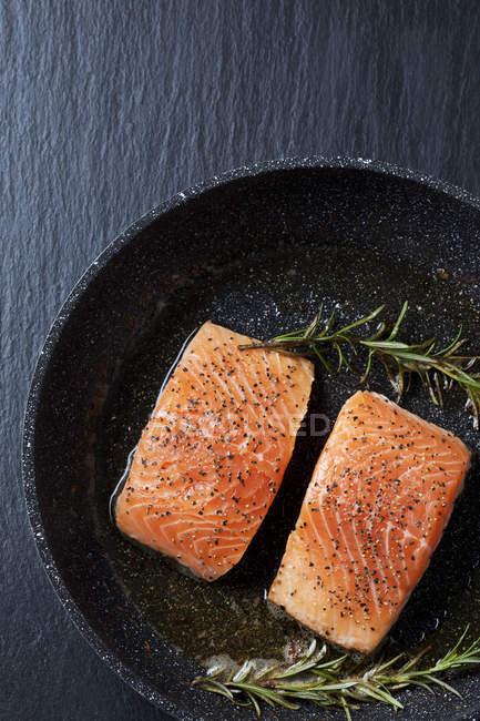 Raw salmon fillets in frying pan — Stock Photo