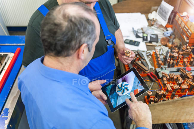 Two men with digital tablet discussing a workpiece — Stock Photo