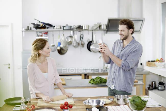 Людина з зображенням стільниковий телефон усміхається жінка приготування тіста для піци за кухня — стокове фото