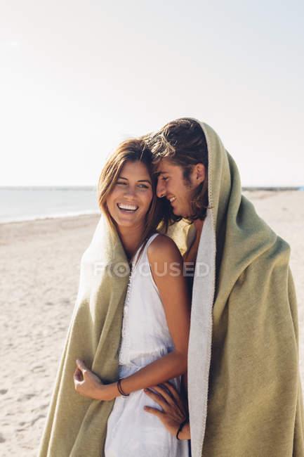 Пара, стоящая вместе на пляже — стоковое фото