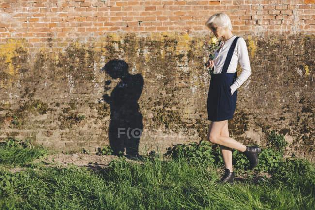 Woman walking along brick wall — Stock Photo