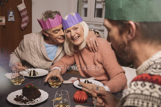 Happy senior couple with paper crowns having Christmas pudding — Stock Photo