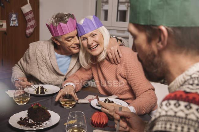 Счастливая пожилая пара с бумажными коронами и рождественским пудингом — стоковое фото