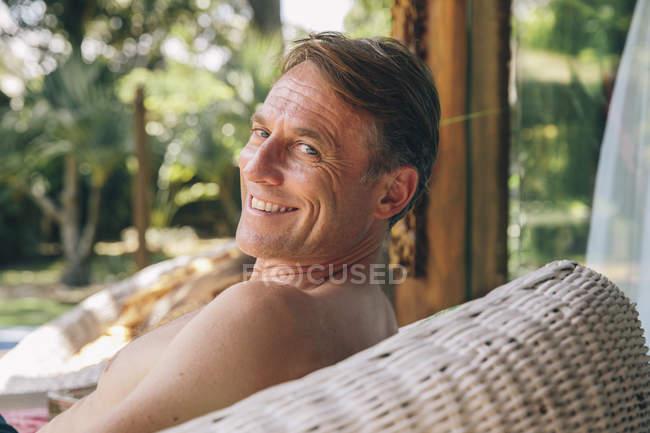 Портрет улыбающийся человек, сидя в кресле корзина на крыльце — стоковое фото