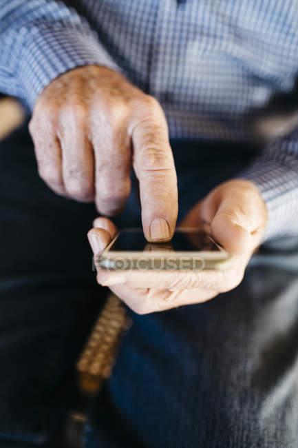 Старшие руки мужчины с помощью смартфона — стоковое фото