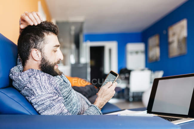Man using laptop and mobile phone — Stock Photo