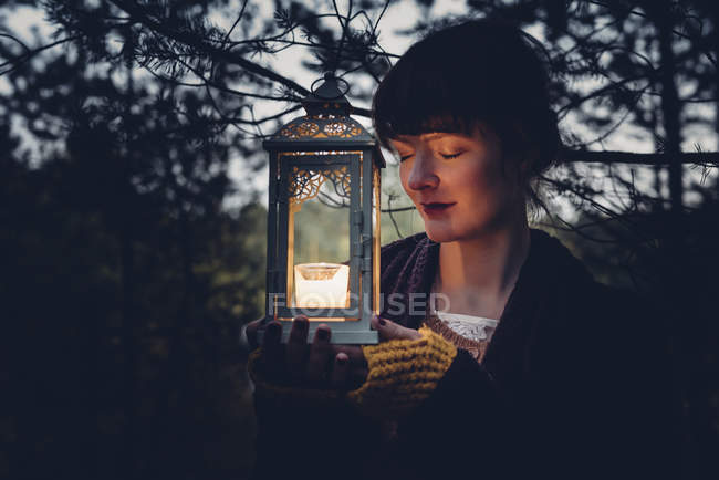 Portrait of woman with closed eyes holding storm lamp, — Stock Photo