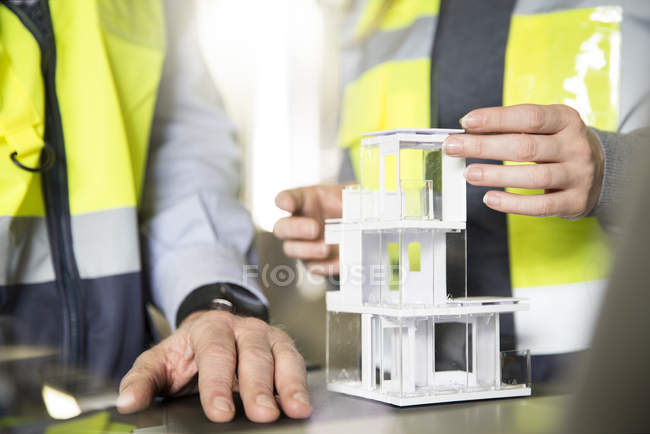 Close-up of colleagues wearing reflective vests with architectural model — Stock Photo