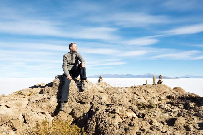 Atacama, Altiplano, Salar de Uyuni, Bolivien, Mann sitzt auf Stein — Stockfoto