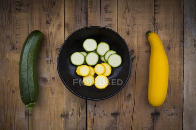 Желтый и зеленый цуккини и миску цуккини ломтиками на дереве — стоковое фото