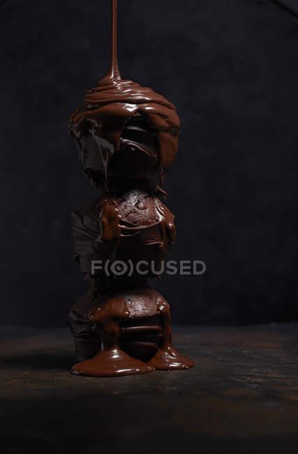 Рідкий шоколад, капала на стек три шоколадні кекси на темному тлі — стокове фото