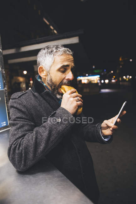 Man eating Cheese Carniolan sausage while looking at smartphone by night — Stock Photo