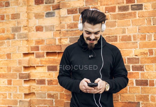 Portrait of young man in front of brick wall listening music with headphones — Stock Photo