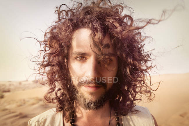 Man with curly hair standing in desert — Stock Photo