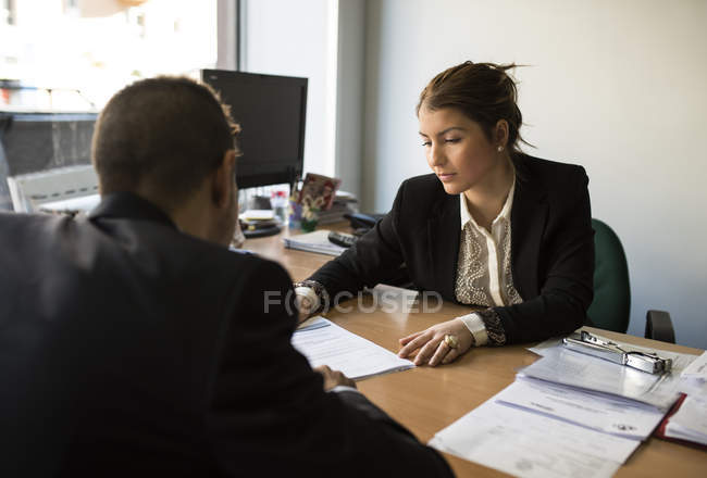 Man and woman in office sitting opposite looking at document — Stock Photo