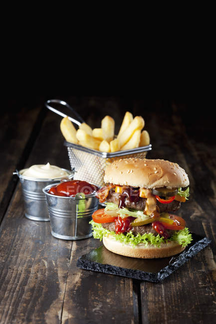 Large hamburger with fries — Stock Photo