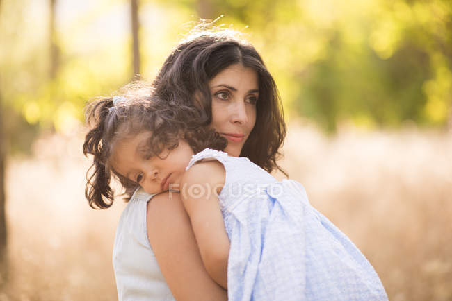 Woman carrying her little daughter — Stock Photo