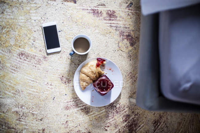 Smartphone, cup of coffee and croissant with jam on the floor — Stock Photo
