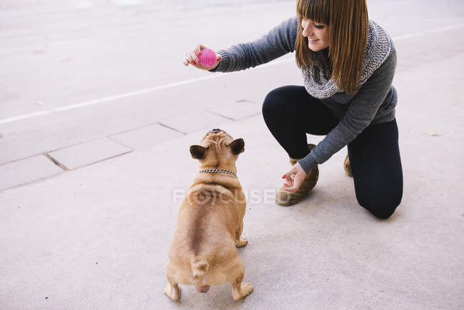 Young woman playing with her French bulldog on pavement — Stock Photo