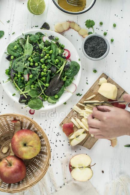 Обрізаний подання рук різання apple поблизу салат — стокове фото