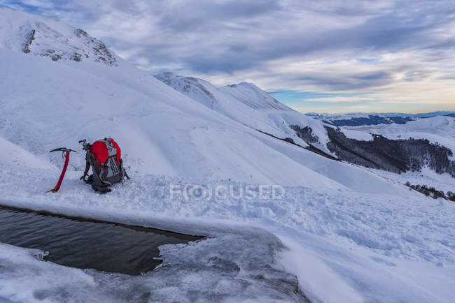 Italia, Umbria, Parco nazionale dei Monti Sibillini, tramonto sul Monte Redentore in inverno, ghiaccio ax e zaino — Foto stock