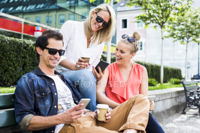 Happy friends sitting on bench and sharing smartphones — Stock Photo