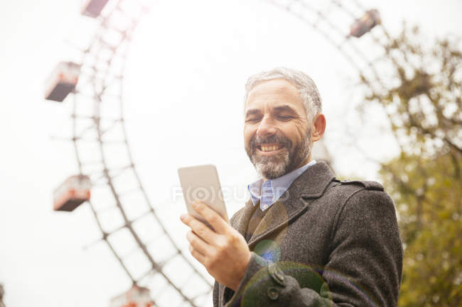 Portrait of smiling businessman looking at his smartphone at Prater — Stock Photo