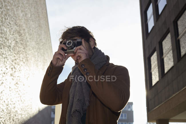 Young man taking a picture with vintage camera — Stock Photo