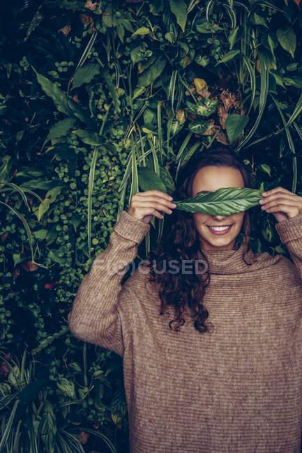 Souriante jeune femme couvrant ses yeux avec une feuille — Photo de stock