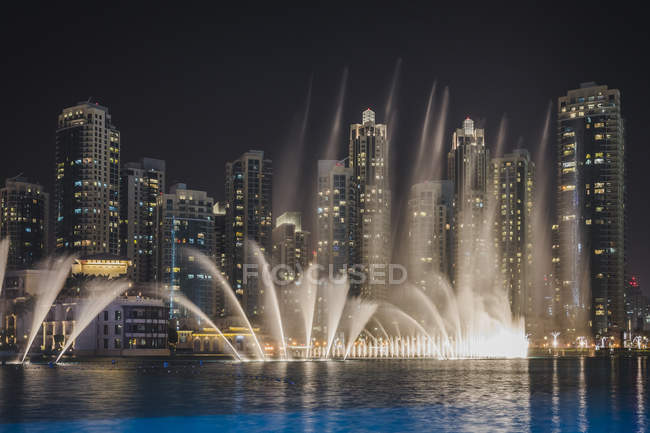 View to skyling by night with trick fountains in the foreground, Dubai, UAE — Stock Photo