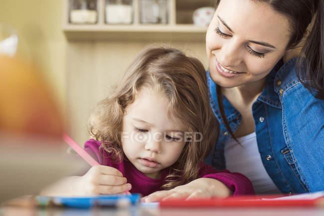 Девушка рисует красочными карандашами — стоковое фото