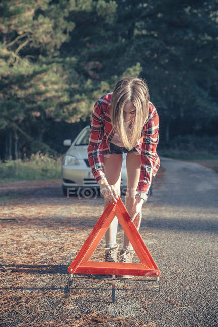 Young woman putting warning triangle on country lane by vehicle breakdown — Stock Photo