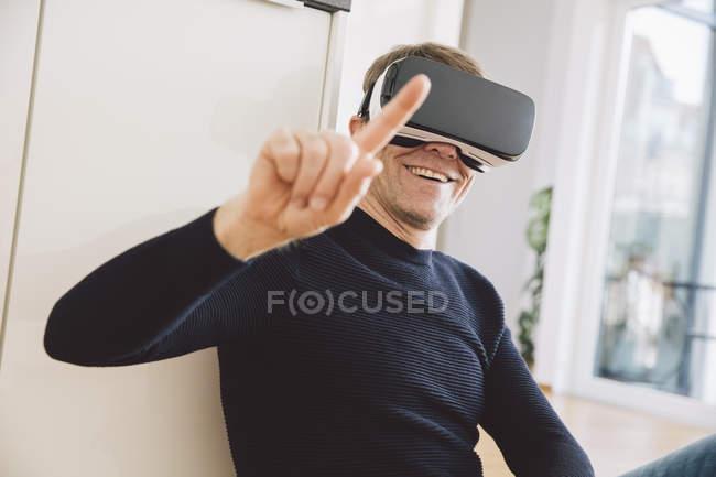 Lächelnder Mann mit Virtual-Reality-Brille zeigt mit dem Finger — Stockfoto
