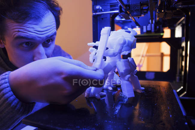 Hombre examinando una figura de un robot impreso por una impresora 3D - foto de stock