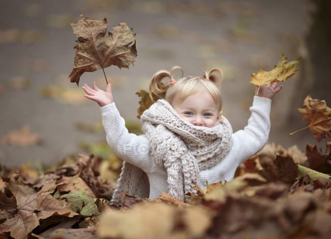 Счастливая девушка блондинка с большой шарф, бросая осенью листья в воздухе — стоковое фото