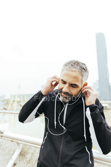 Reifer Athlet mit Kopfhörern bereitet sich auf den Lauf vor — Stockfoto