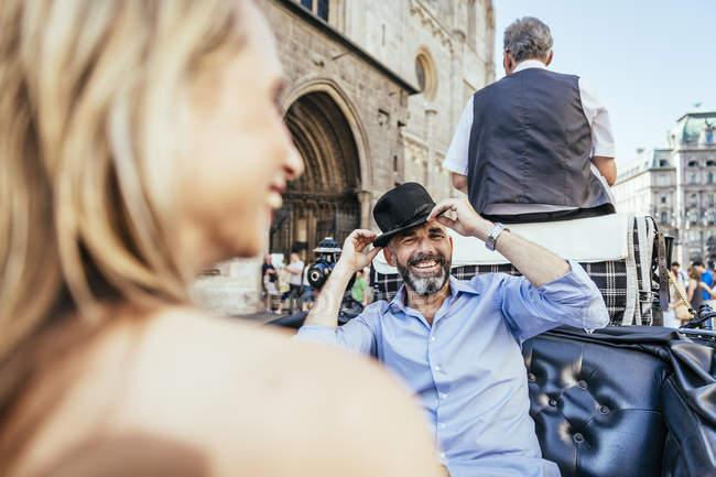 Couple having fun on sightseeing tour in horse cab, man trying on a hat — Stock Photo