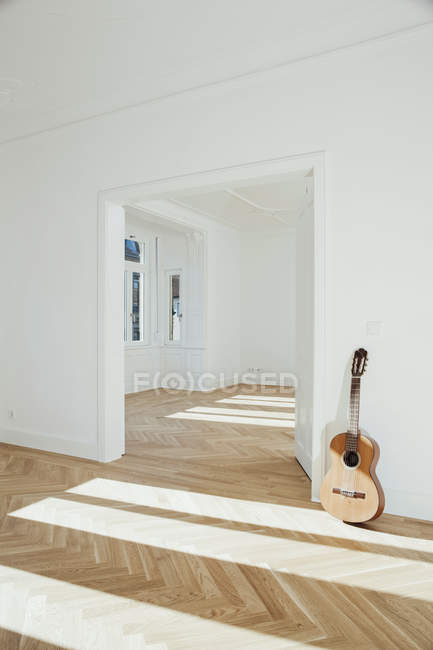Guitar leaning on wall — Stock Photo